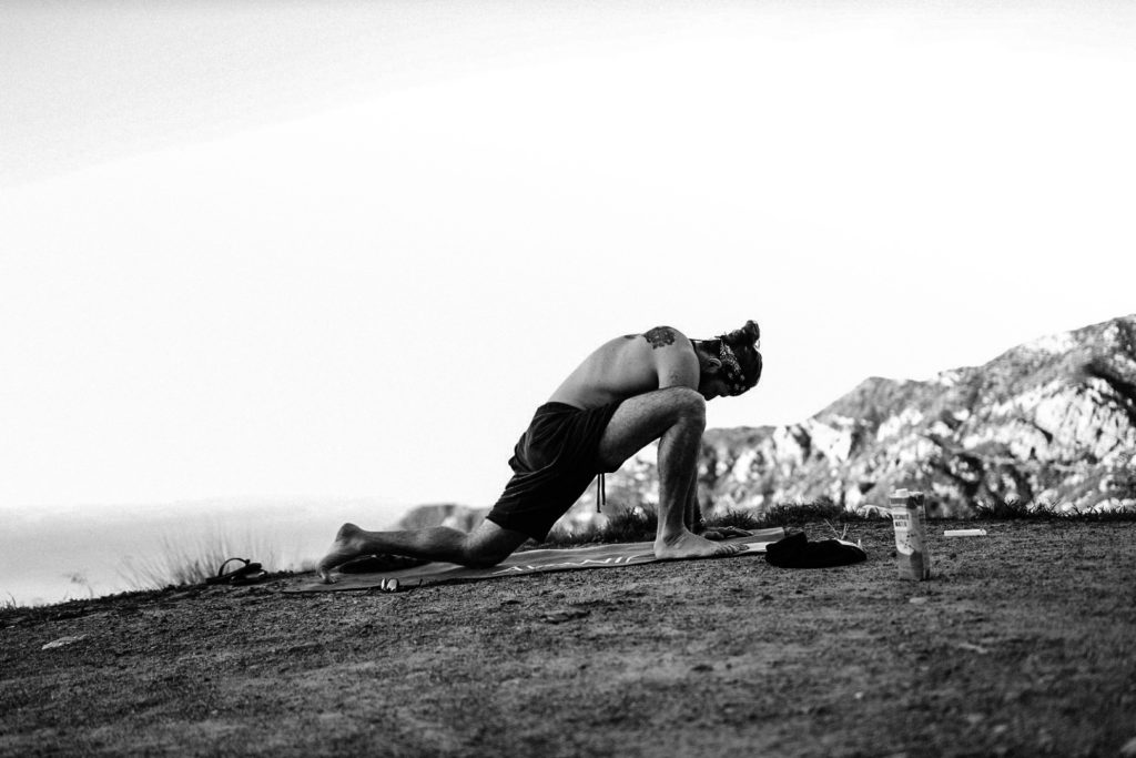 Man performing yoga lunge on beach in LA
