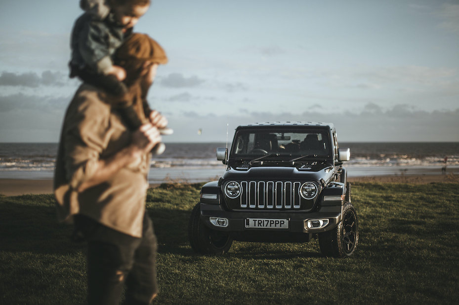 Dad with son on shoulders on the beach looking at their jeep